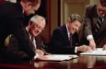 08 grudnia 1987 r., Waszyngton, DC, USA --- Prezydent Ronald Reagan i radziecki sekretarz generalny Michaił Gorbaczow podpisują porozumienie o kontroli zbrojeń zakazujące użycia pocisków nuklearnych średniego zasięgu, Traktat o redukcji średnich sił jądrowych.  --- Zdjęcie © Bettmann / CORBIS